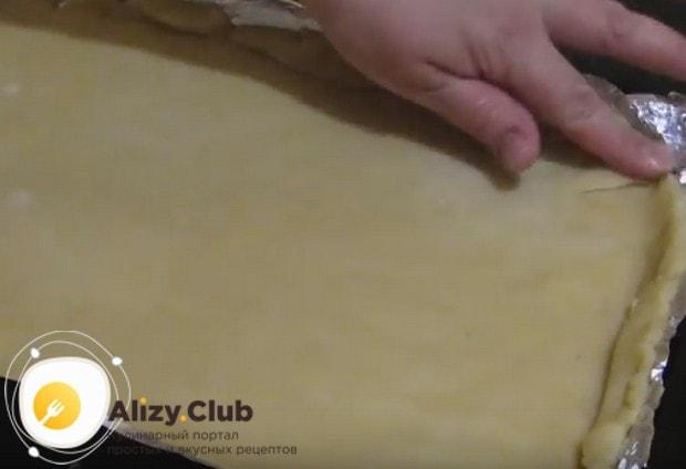 Застелив противень фольгой или пергаментом, выкладываем на нее тесто и делаем маленькие бортики.