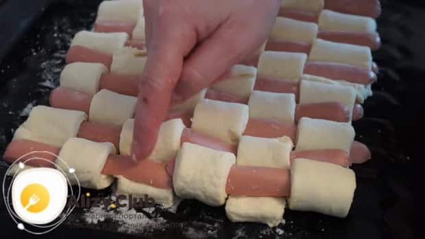 Выложите сосиски в слоеном тесте на противень
