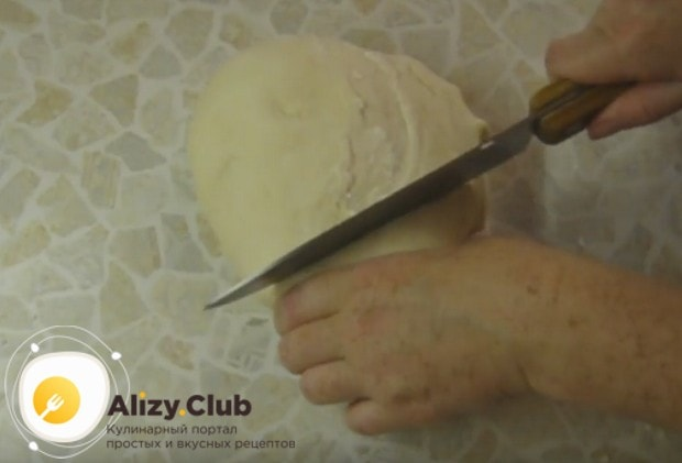Обминаем тесто и делим его на большую и меньшую части.