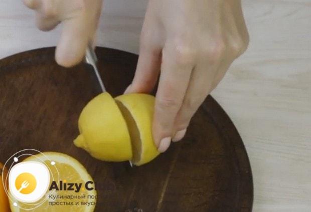 Разрезаем пополам один лимон и один апельсин.