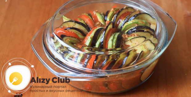Овощи залейте заправкой, накройте форму крышкой или фольгой