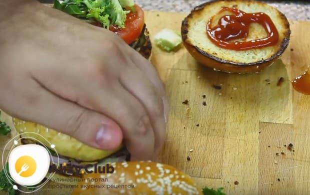 Смазав верхнюю часть булочки кетчупом, накрываем ею бургер и слегка прижимаем.