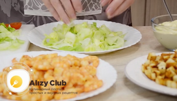 По простому рецепту для приготовления классического салата цезарь с креветками, подготовьте салат