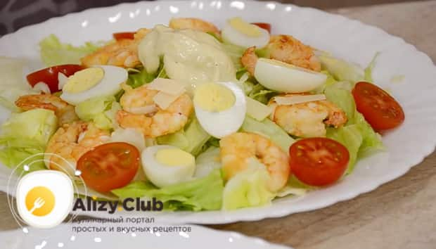 По простому рецепту для приготовления классического салата цезарь с креветками, выложите ингредиенты на тарелку