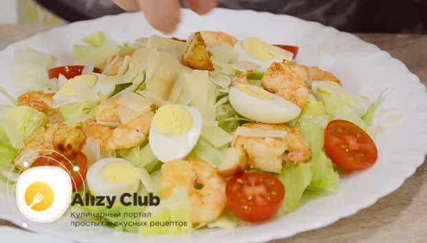 По простому рецепту для приготовления классического салата цезарь с креветками, посыпьте салат сыром