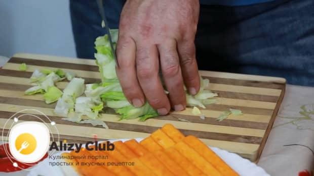 Для приготовления салата с креветками, кальмарами и крабовыми палочками нарежьте капусту