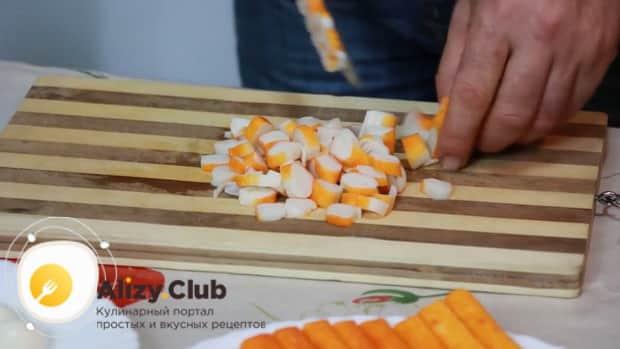 Для приготовления салата с креветками, кальмарами и крабовыми палочками нарежьте все ингредиенты