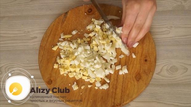 Для приготовления салата с пекинской капустой кукурузой и колбасой нарежьте яйца