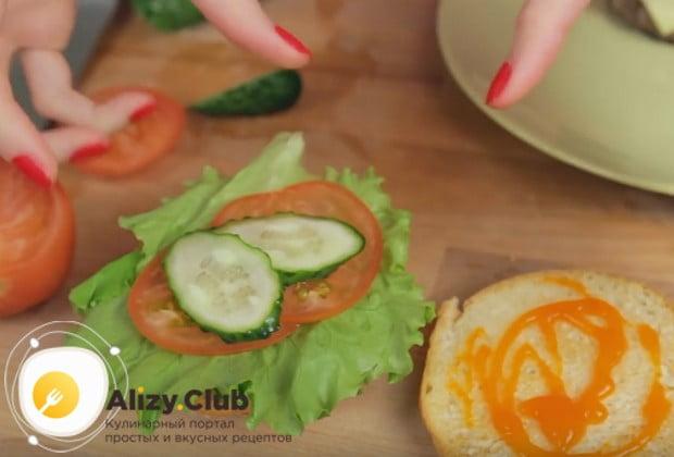 На верхнюю часть булочки кладем лист салата, кружочки помидора и огурца.