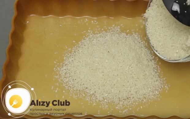 Глубокую форму для запекания смазываем растительным маслом и выкладываем в нее рис.