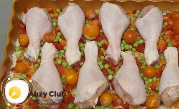 Раскладываем куриные голены, а между ними помещаем помидорки черри.