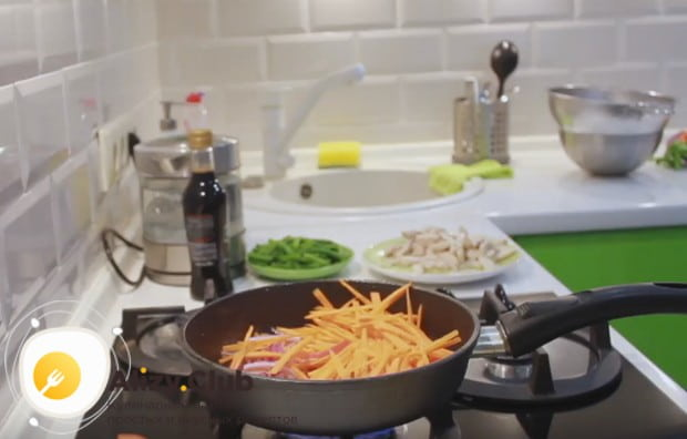 Через несколько минут добавляем к луку морковку.