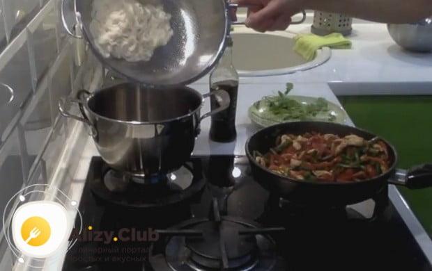 Готовую лапшу откидываем на дуршлаг, перекладываем в кастрюлю и заправляем соевым соусом.