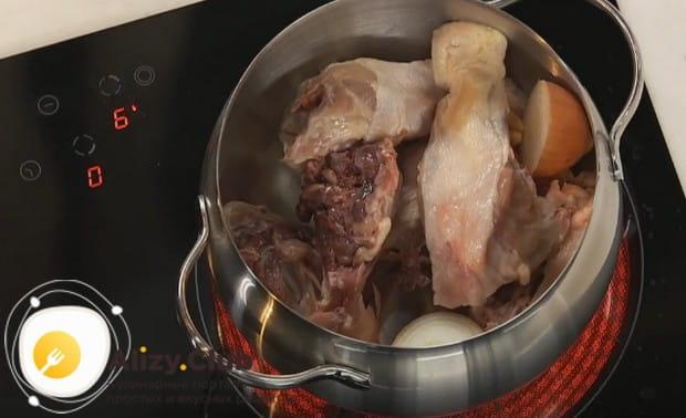 Добавляем к курице разрезанную пополам луковицу.
