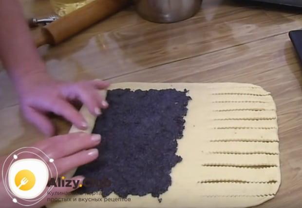 Сделав на трети раскатанного теста надрезы, выкладываем на основную его площадь начинку и сворачиваем до надрезов.
