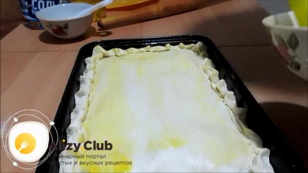 По рецепту для приготовления пирога с сайрой и рисом смажьте тесто яйцом