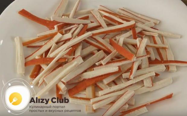 Выкладываем на блюдо нарезанные соломкой крабовые палочки.