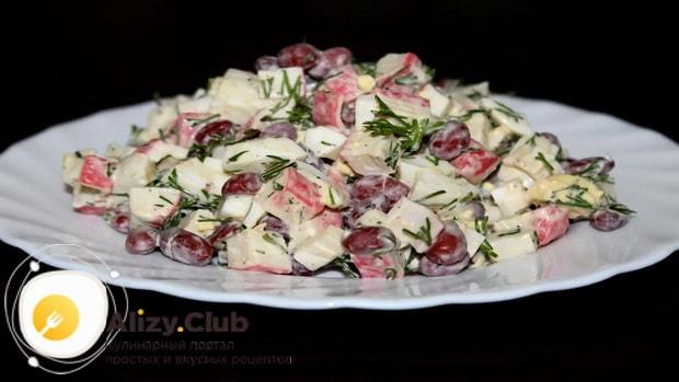Для приготовления салата с фасолью консервированной и крабовыми палочками, перемешайте ингредиенты с соусом