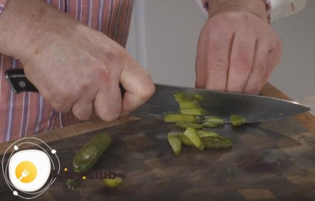 Добавляем в блюдо нарезанный соломкой маринованный огурец.