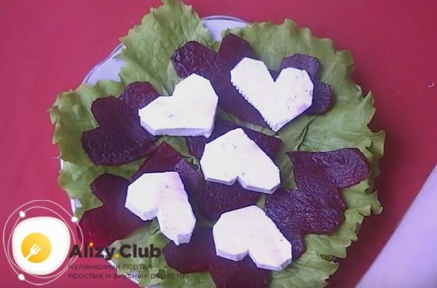 Поверх листьев салата раскладываем кусочки свеклы и сыра.