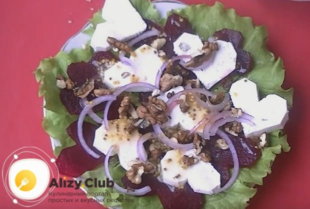 Посыпаем салат луком, грецкими орехами и поливаем соусом.