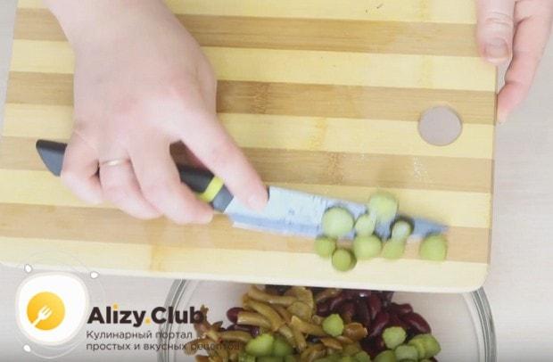 Добавляем огурцы в миску с фасолью и грибами.