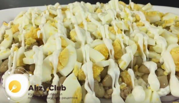 Покрываем фасоль слоем измельченных яиц и смазываем их майонезом.
