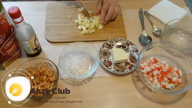 Для приготовления салата с креветками и ананасом и сыром нарежьте ингредиенты