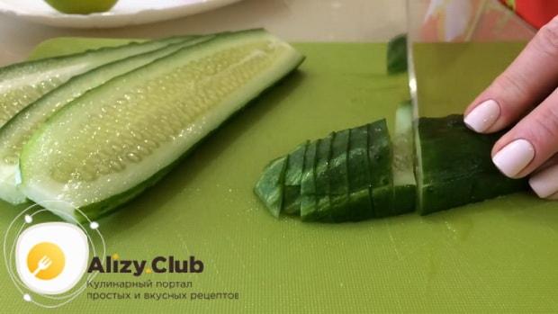 Для приготовления салата с пекинской капустой и ветчиной, нарежьте огурцы