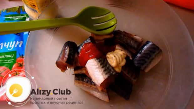 Для приготовления скумбрии запеченной в духовке с картошкой, по рецепту, смешайте рыбу с кетчупом