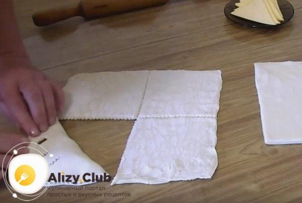 Накрываем свободной частью теста сыр и защипываем края пирожка.