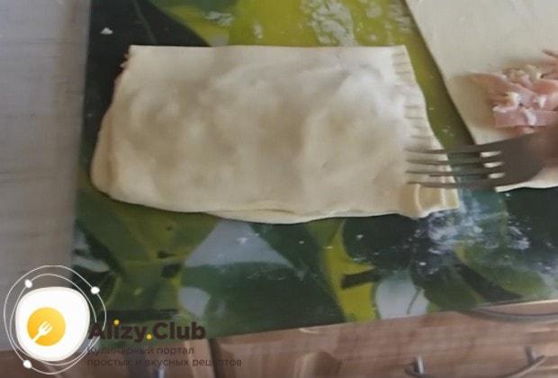 Накрываем начинку свободной половиной теста и проходимся по краю получившегося пирожка вилкой.