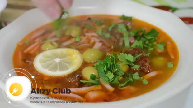 Готовую солянку разливаем по тарелкам, добавляем нарезанные колбасу