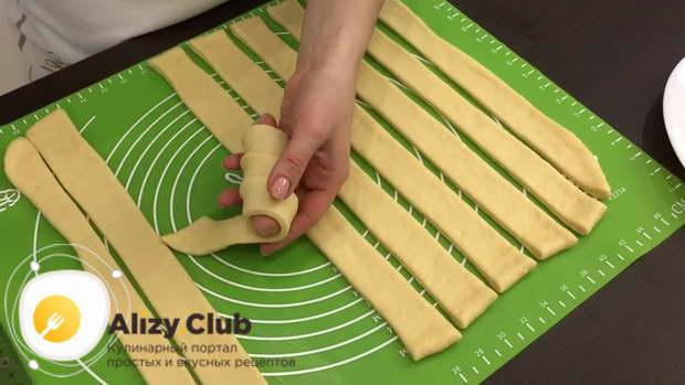 Пальцем распределите край полосы, чтобы она прилипла к сосиске