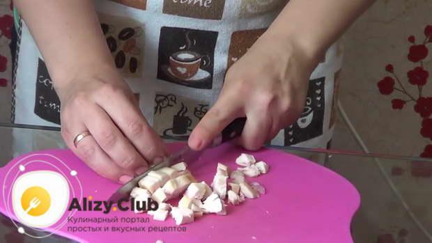 Копченую куриную грудинку порежьте небольшими кубиками