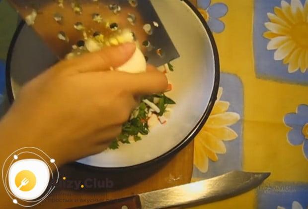 На крупной терке натираем в начинку сваренные вкрутую яйца.