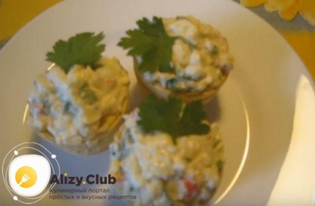 Тарталетки с яйцом и крабовыми палочками будут выглядеть нарядней, если украсить их листиком петрушки.
