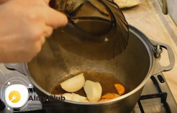 Выкладываем в казан лук и морковь.