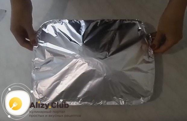 Смазав утку растительным маслом, накрываем ее фольгой и отправляем в духовку запекаться.