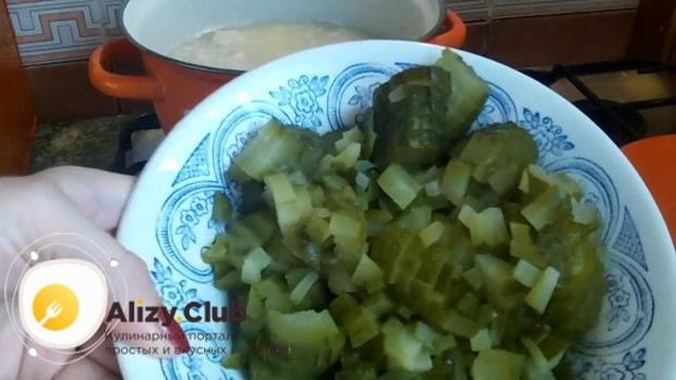 По рецепту для приготовления рассольника с рисом и солеными огурцами, нарежьте огурцы