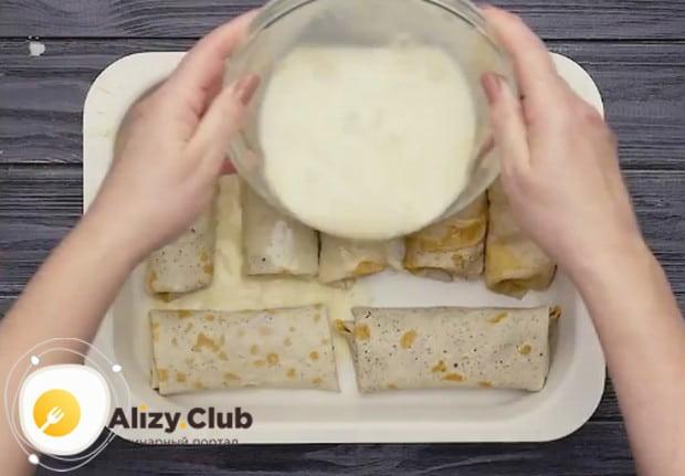 Заливаем блины в форме сметанным соусом.