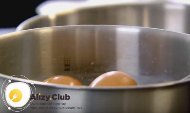 Кипятим в кастрюлю воду и опускаем в нее яйца.