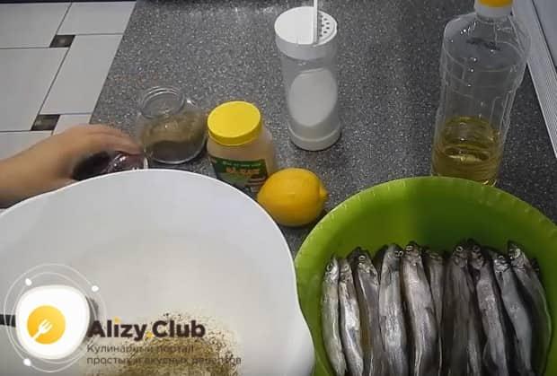Приготовим панировку для мойвы на основе муки, соли и перца.