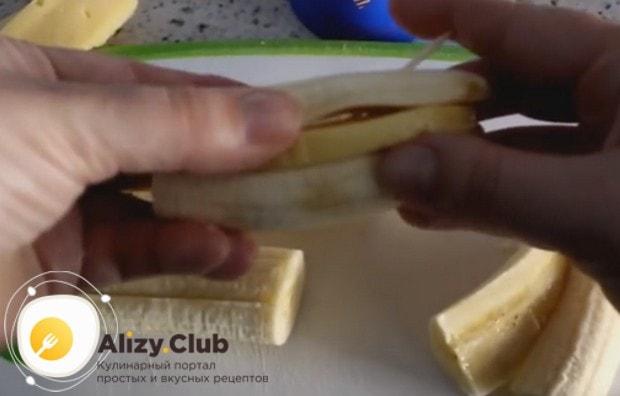 Разрезав половинки бананов пополам, кладем между ними ломтики сыра и скрепляем такую конструкцию зубочистками.