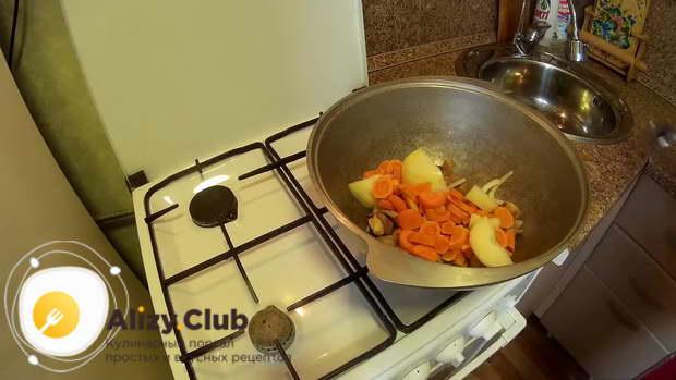 Выкладываем в казан подготовленный лук, морковь