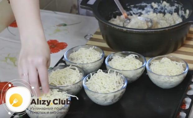 Раскладываем жульен в порционные кокотницы и посыпаем сыром.