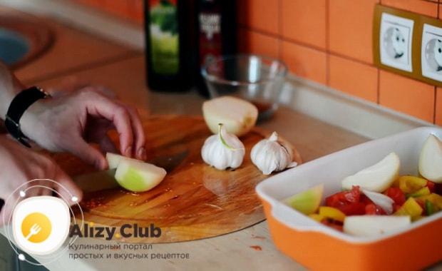 Для приготовления курицы с овощами в духовке нарежьте лук
