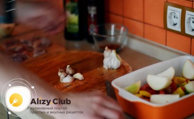 Для приготовления курицы с овощами в духовке нарежьте чеснок
