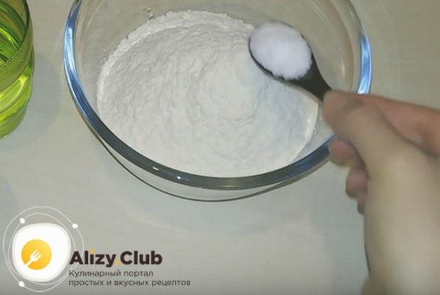 Чтобы приготовить заварное тесто для вареников без яиц, в просеянную муку добавляем соль.