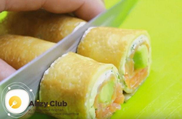 Нарезаем наши блины с красной рыбой и сливочным сыром на небольшие порционные кусочки.